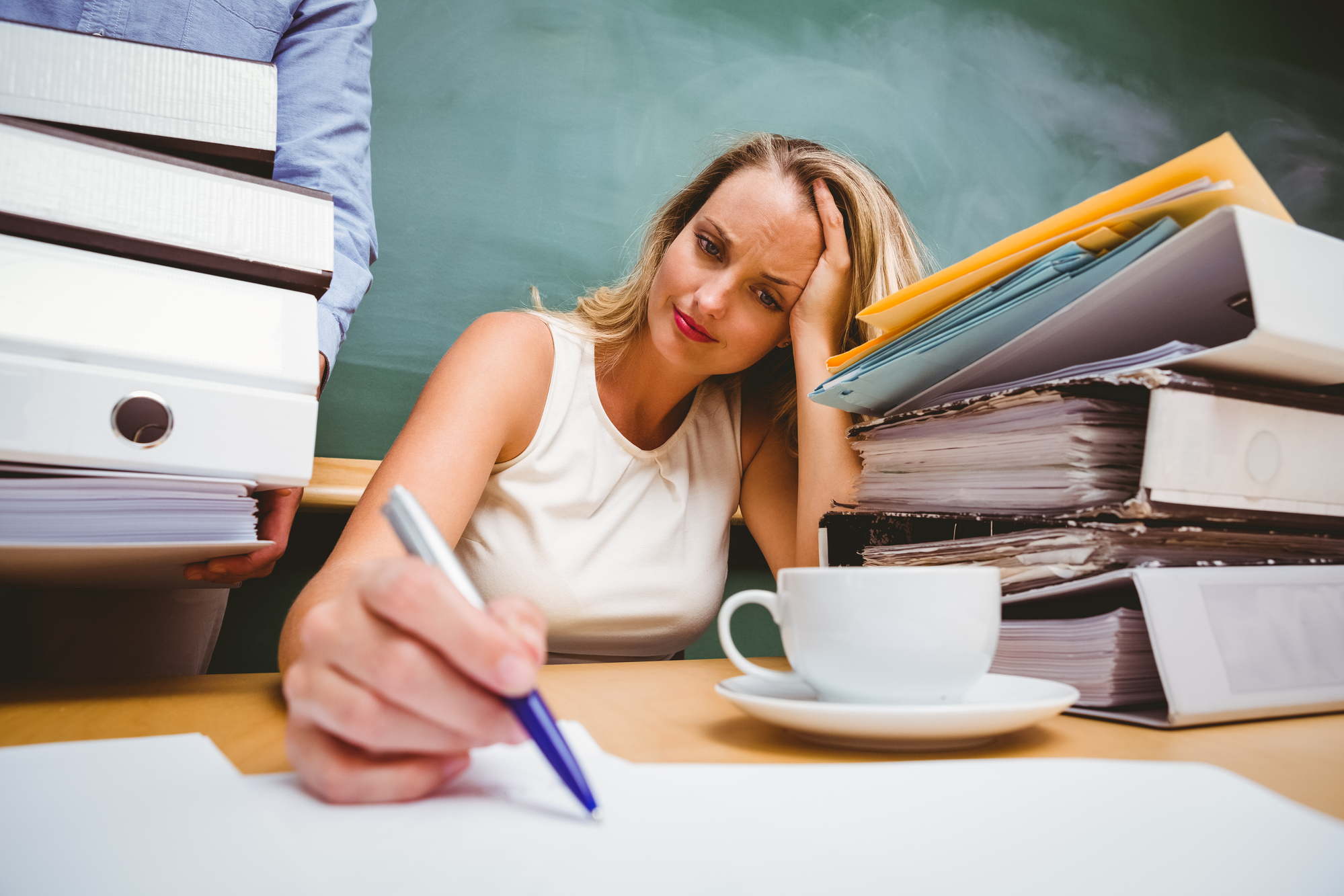 Beautiful young businesswoman writing document at office desk