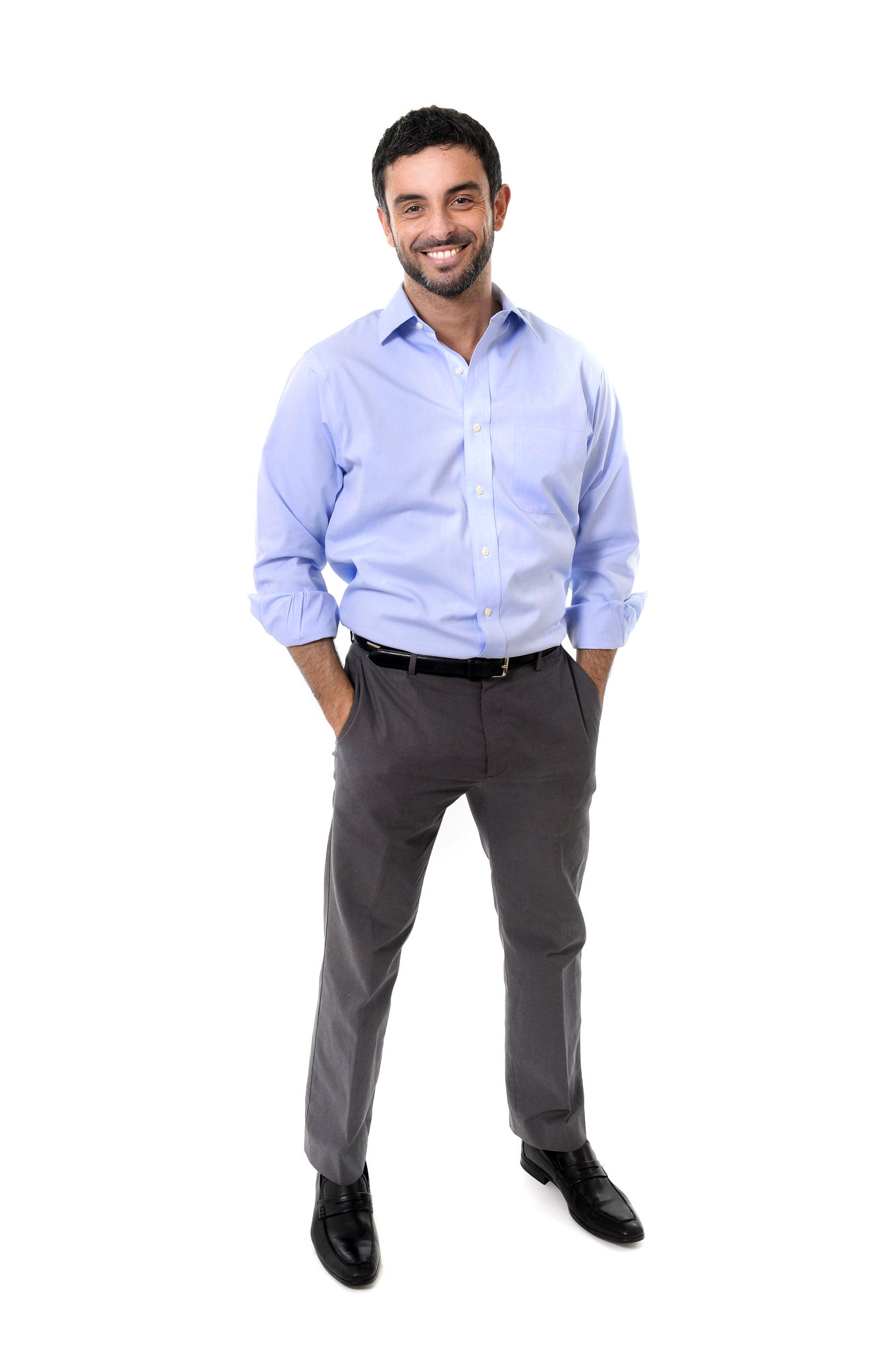 young attractive business man standing in corporate portrait isolated on white background smiling with hands in pockets wearing shirt and suit trousers